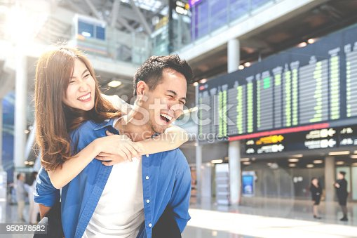 istock Happy young asian couple tourist having fun, enjoy at airport terminal. Lover student smile with summer travel in vacation holiday. Honeymoon trip concept. 950978582