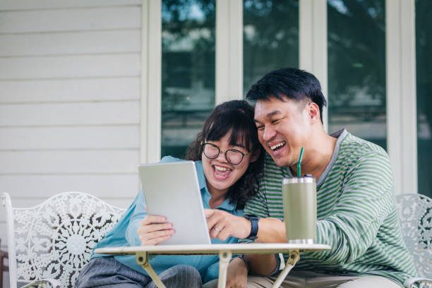 happy young asian couple using digital tablet while sitting in front of the house, couple relaxing and spending time together in backyard at home, people and lifestyle concept - young girl computer home front imagens e fotografias de stock