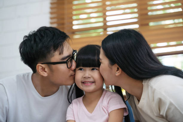 Happy young asian father and mother are kissing her daughter's cheek. Happy family enjoy spending a good time together in a house. Happy asian family. Happy young asian father and mother are kissing her daughter's cheek. Happy family enjoy spending a good time together in a house. Happy asian family. little girl kissing dad on cheek stock pictures, royalty-free photos & images