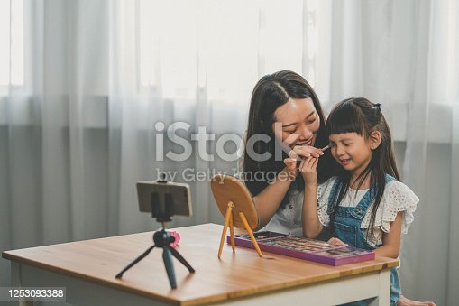 Image of Happy Young Asian mother applying make-up to her daughter on social media together at home.