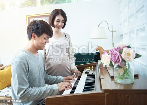 869795984 istock photo Happy young asian pregnant woman stand side of man play piano at home. 1213145100