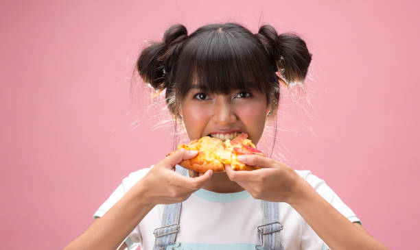 Happy young asian woman eating slice of pizza stock photo
