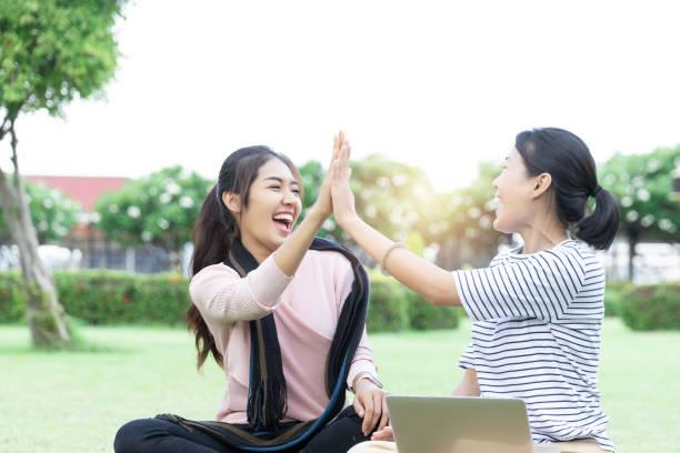 Feliz joven mujer asiática dando cinco altos a los colegas después de recibir buenas noticias de la computadora portátil. Las mujeres están emocionadas con trabajar juntos con éxito. éxito y ganar - foto de stock