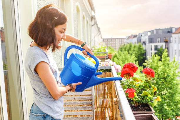 Happy Young Asian Woman Hausfrau Bewässerung Blumen auf Balkon – Foto