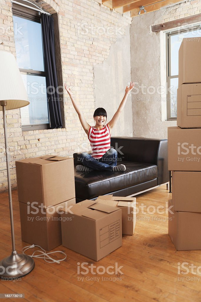 Happy Young Asian Woman Moving Boxes Into Loft Apartment Home royalty-free stock photo