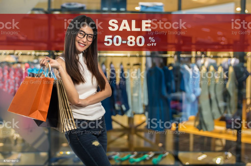 Happy young asian woman shopping and holding the product paper bag over Sale 50-80% off mock up advertise display frame setting over the Abstract blurred photo of clothing store stock photo