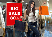 Happy young asian woman shopping and holding the product paper bag over sale 80% off mock up advertise display frame setting with the clothes wear in model in the shopping department store.