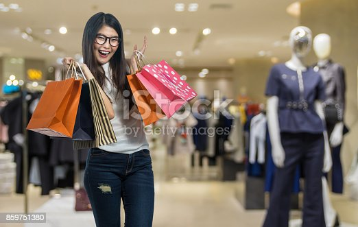 istock Happy young asian woman shopping in happy feeling and holding the product paper bag over the Abstract blurred photo of clothing store in a shopping mall, shopping concept 859751380