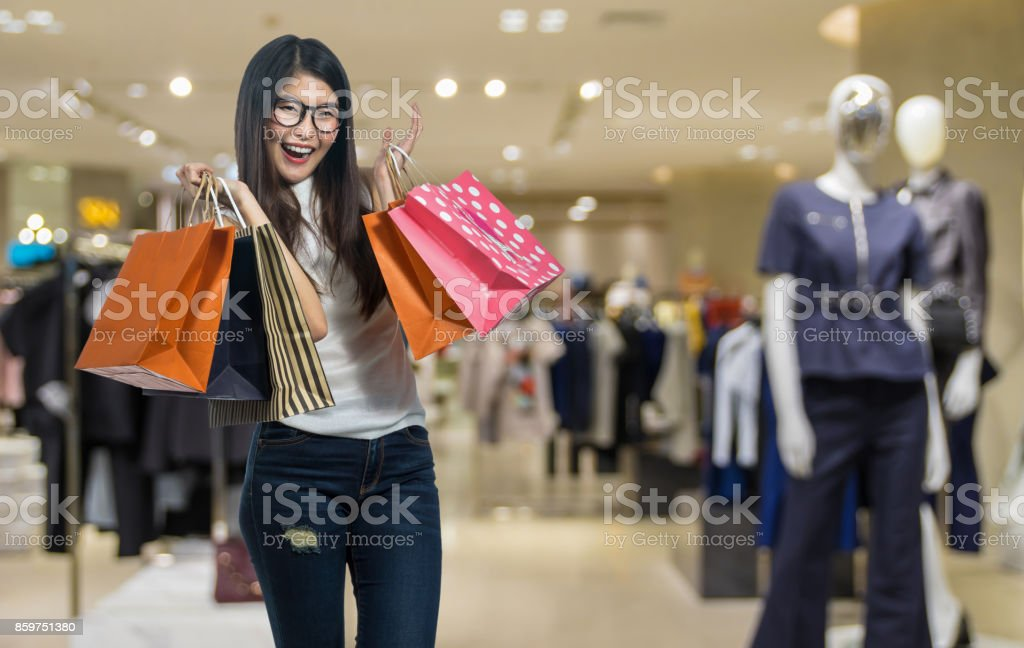 Happy young asian woman shopping in happy feeling and holding the product paper bag over the Abstract blurred photo of clothing store in a shopping mall, shopping concept - fotografia de stock