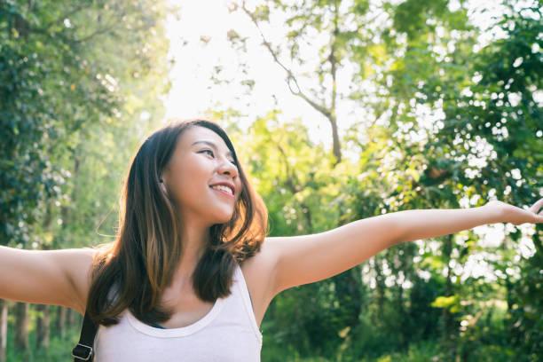 Glückliche junge asiatische Reisende mit Rucksack zu Fuß in Wald. Wanderasiatische Frau mit Rucksack zu Fuß auf dem Weg im Sommerwald. Adventure Backpacker Travel Menschen concept. – Foto