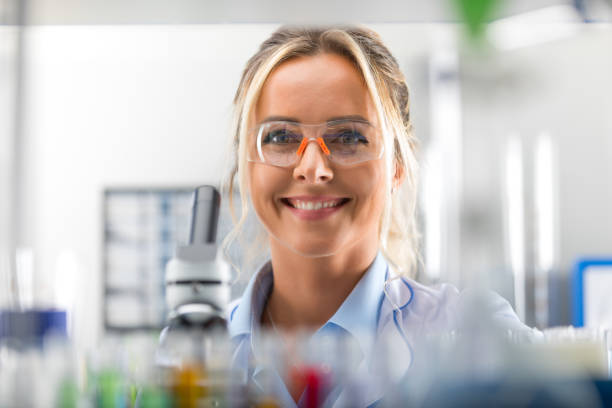 Happy young attractive smiling woman scientist in the laboratory stock photo