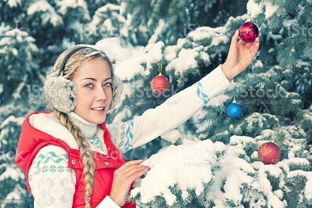 Happy Young Attractive Woman Decorating Christmas Tree in a Park stock photo