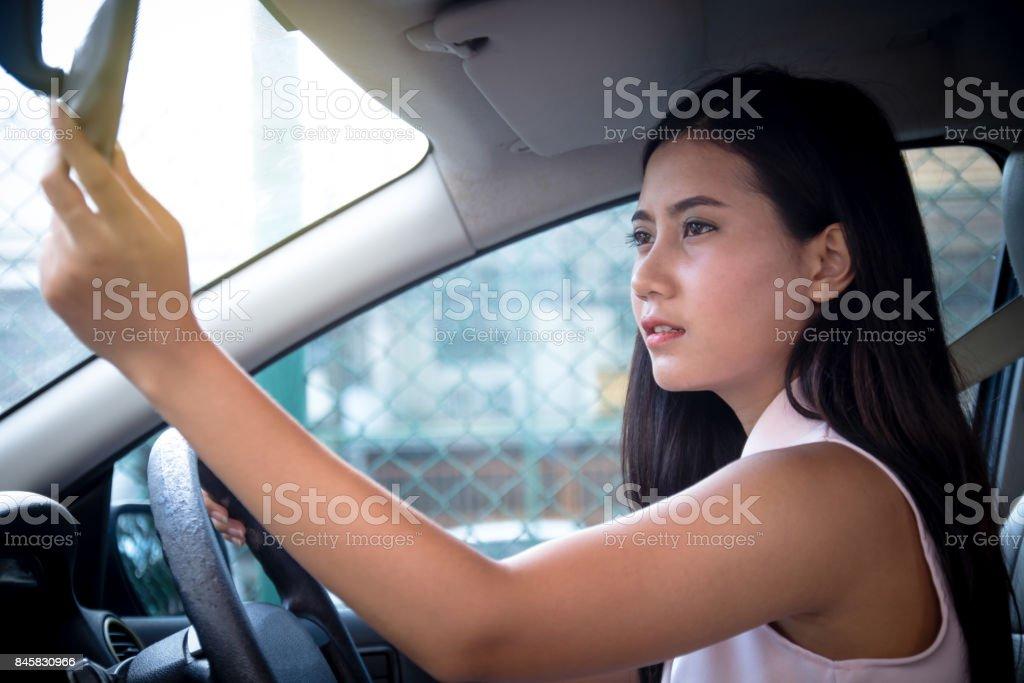 Driver de mulher atraente jovem feliz sentado na cadeira lá dentro do carro, usando a mão para ajustar o espelho retrovisor do carro, faça a investigar. - foto de acervo