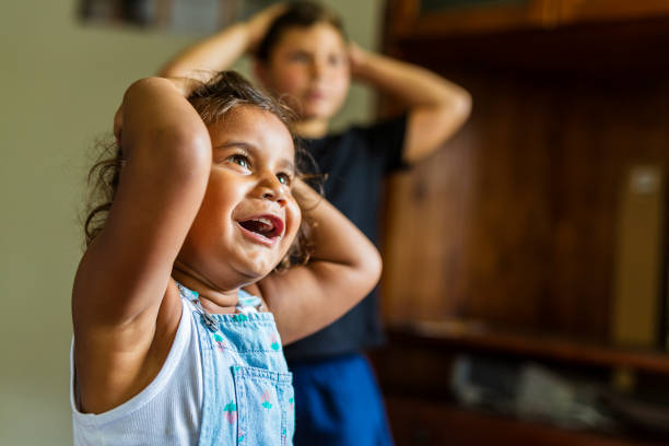 Happy Young Australian Aboriginal Girl Learning to Sing and Dance to a Song stock photo