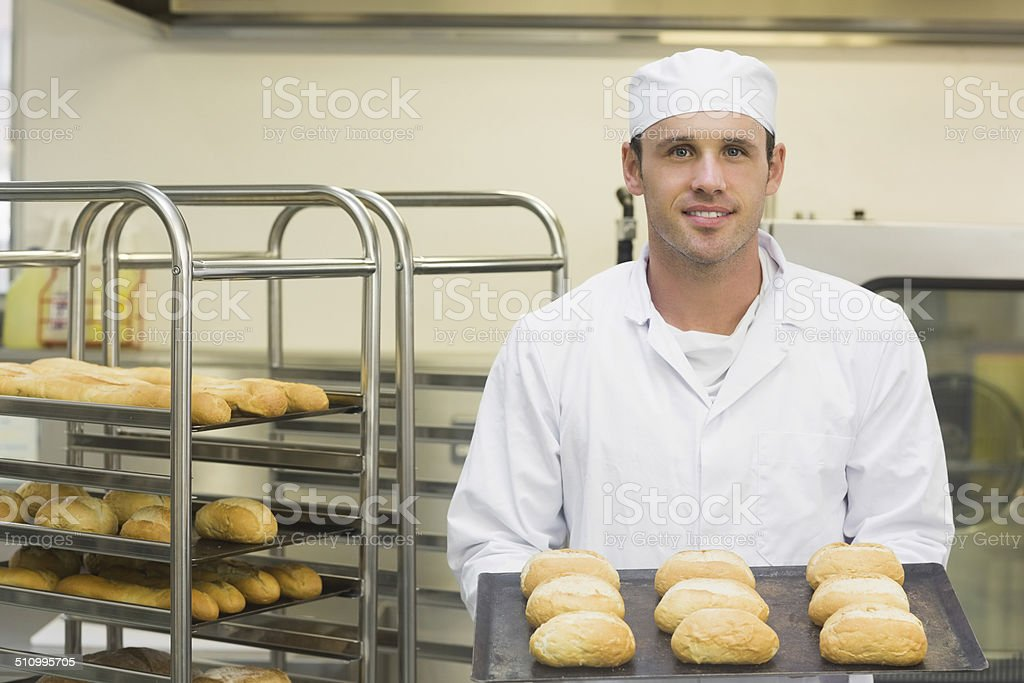 Happy young baker holding some rolls on a baking tray stock photo