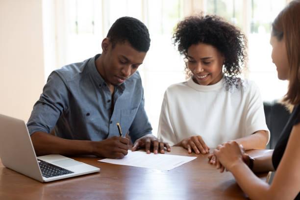glückliche junge bankangestellte beobachten afrikanische ethnische zugehörigkeit kunden unterzeichnung vertrag. - unterschrift stock-fotos und bilder