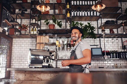 istock Happy young bar owner standing at the counter 579128186