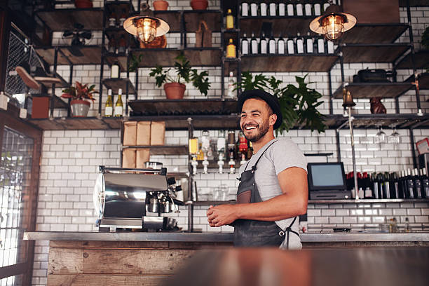 Happy young bar owner standing at the counter stock photo