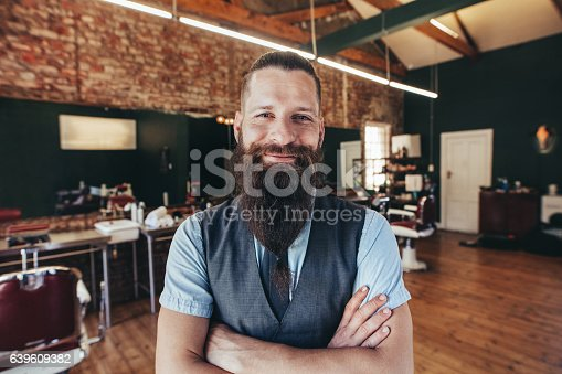 istock Happy young barber smiling at his barbershop 639609382