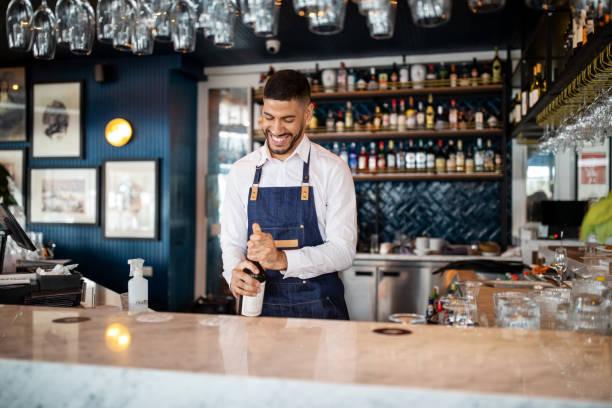 Glücklicher junger Barmann, der an der Bar arbeitet – Foto