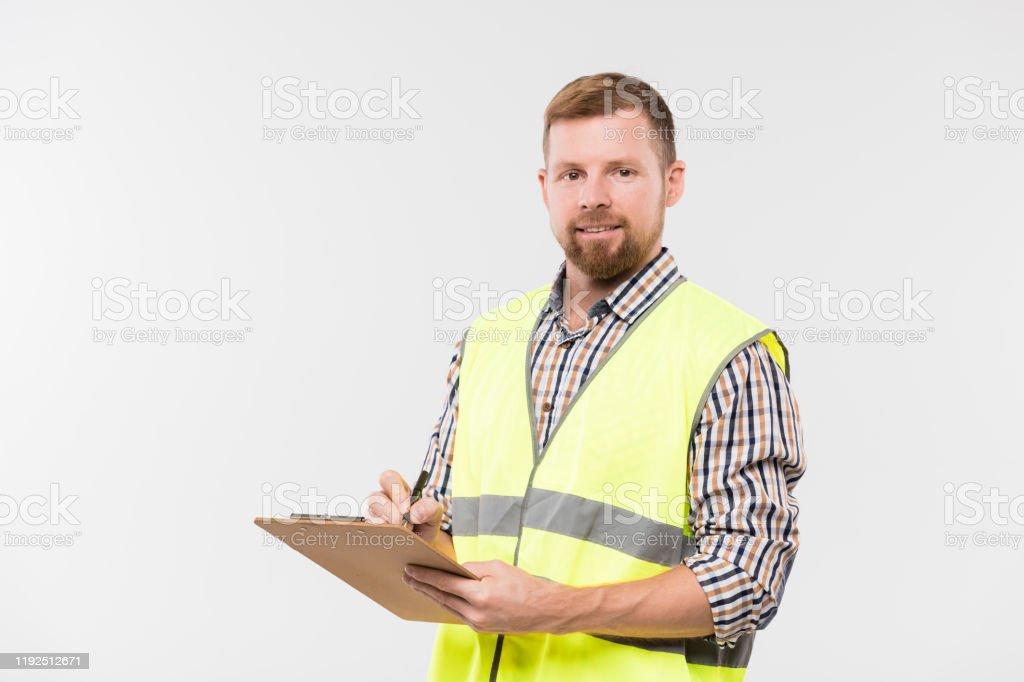 Glücklicher junger bärtiger Ingenieur mit Zwischenablage und Stift, der Arbeitsnotizen macht - Lizenzfrei Arbeiten Stock-Foto