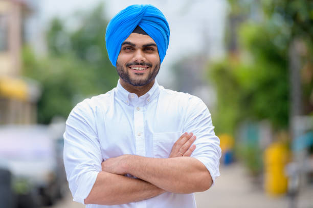 Happy young bearded Indian Sikh man smiling outdoors stock photo
