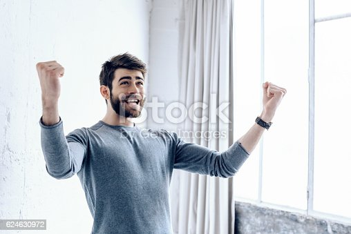 istock happy young bearded man cheering  in Paris loft appartment 624630972