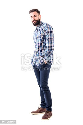 931173966istockphoto Happy young bearded man in checked shirt with hands in pockets smiling and looking at camera 947281944