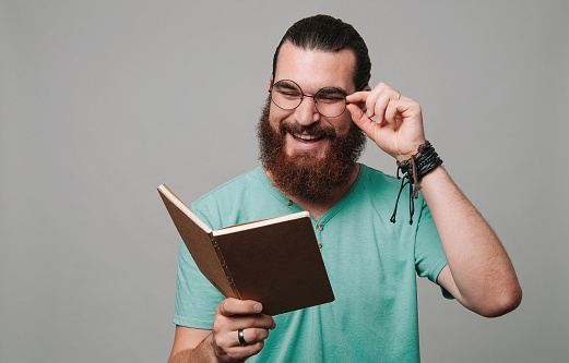 Happy young bearded man reading a book and smiling over grey background