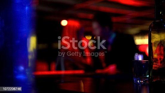 istock Happy young beautiful couple dating in nightclub, woman kissing man, defocused 1072206746
