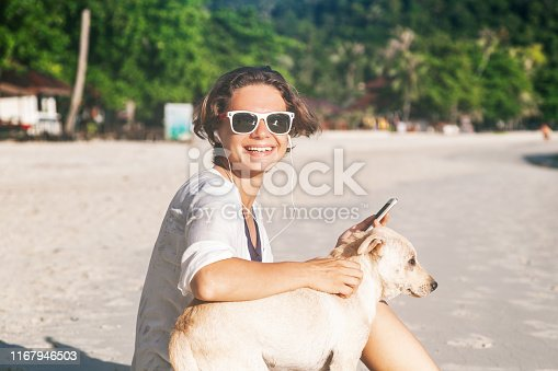 Happy young beautiful funny girl on the beach  with a dog. Vacation, travel, joy, freedom, internet, technology concept