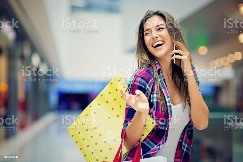 Happy, young beautiful girl is talking in the Mall stock photo