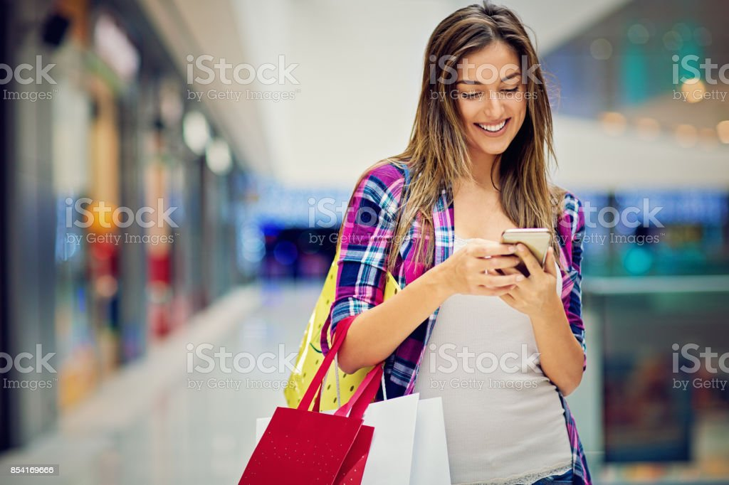 Happy, young beautiful girl is texting in the Mall stock photo