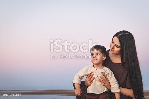 Happy young beautiful mother with her son three years old admiring the sunset on the beach. Family look linen clothes. Copy space