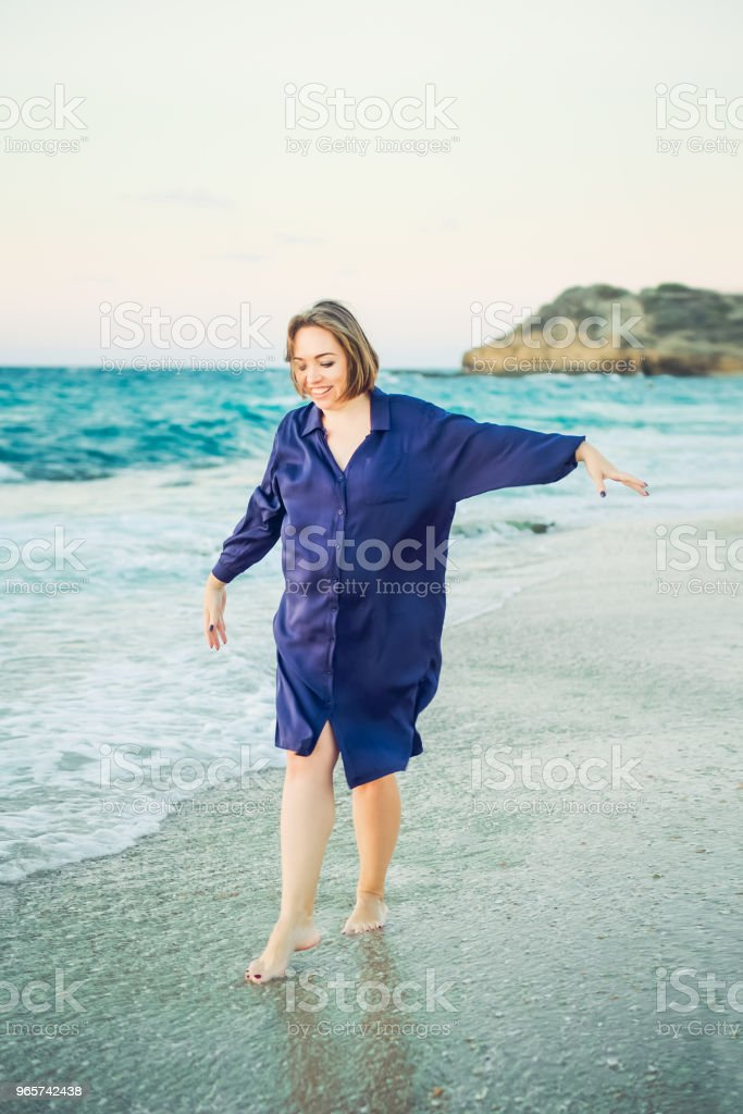 Happy young beautiful pregnant woman in dark blue dress raising her arms and walking and on the beach. Relax by the calm sea in sunshine. soft selective focus, space for text. - Royalty-free Baby - Human Age Stock Photo