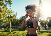 Smiling young woman enjoying listening to music on earphones in the park on a sunny day