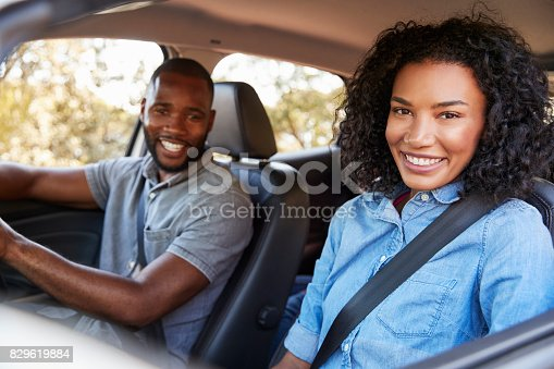 istock Happy young black couple driving in a car smiling to camera 829619884