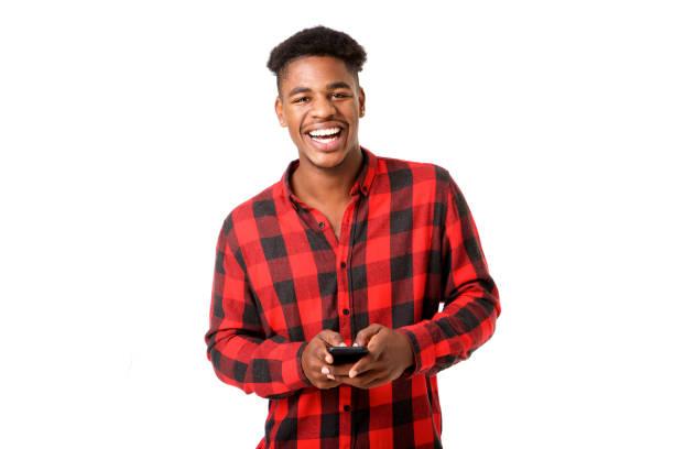 Glücklicher junger schwarzer Mann hält Handy vor weißem Hintergrund – Foto