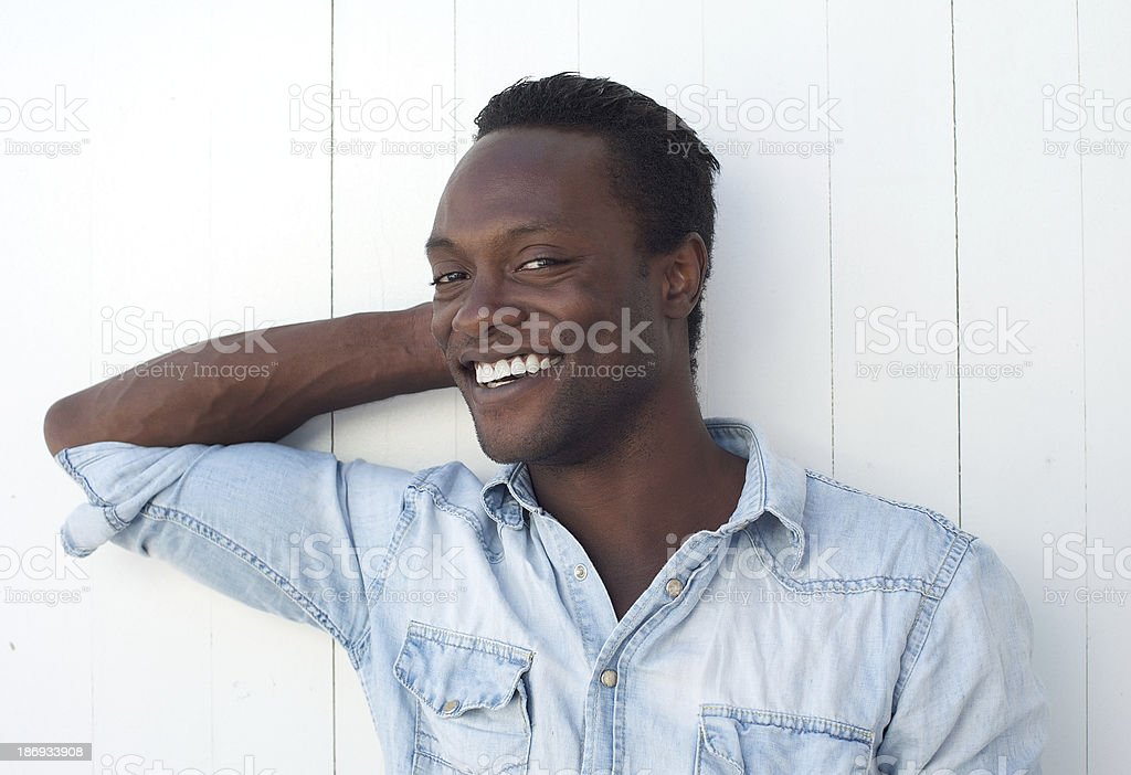 Happy young black man smiling against white background outdoors royalty-free stock photo