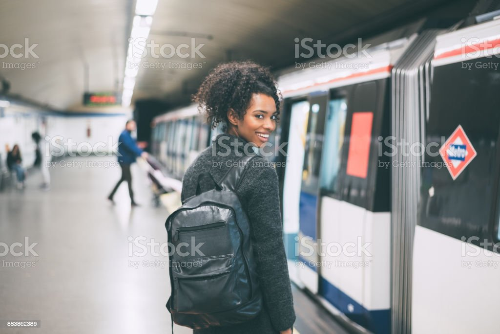Happy young black woman inside the underground station waiting for the train 'n stock photo