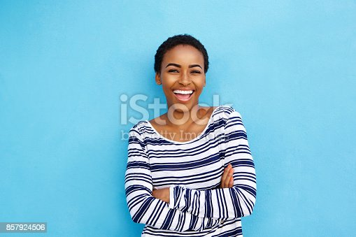 istock happy young black woman laughing against blue wall 857924506