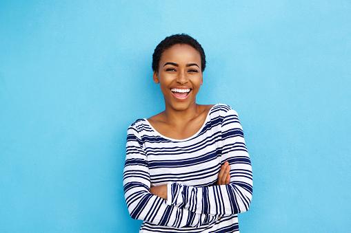快樂的年輕黑人婦女笑牆上藍色 照片檔及更多 20多歲 照片