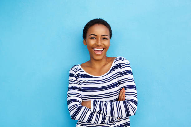 happy young black woman laughing against blue wall stock photo