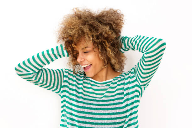 happy young black woman laughing with hand in hair Portrait of happy young black woman laughing with hand in hair hand in hair stock pictures, royalty-free photos & images