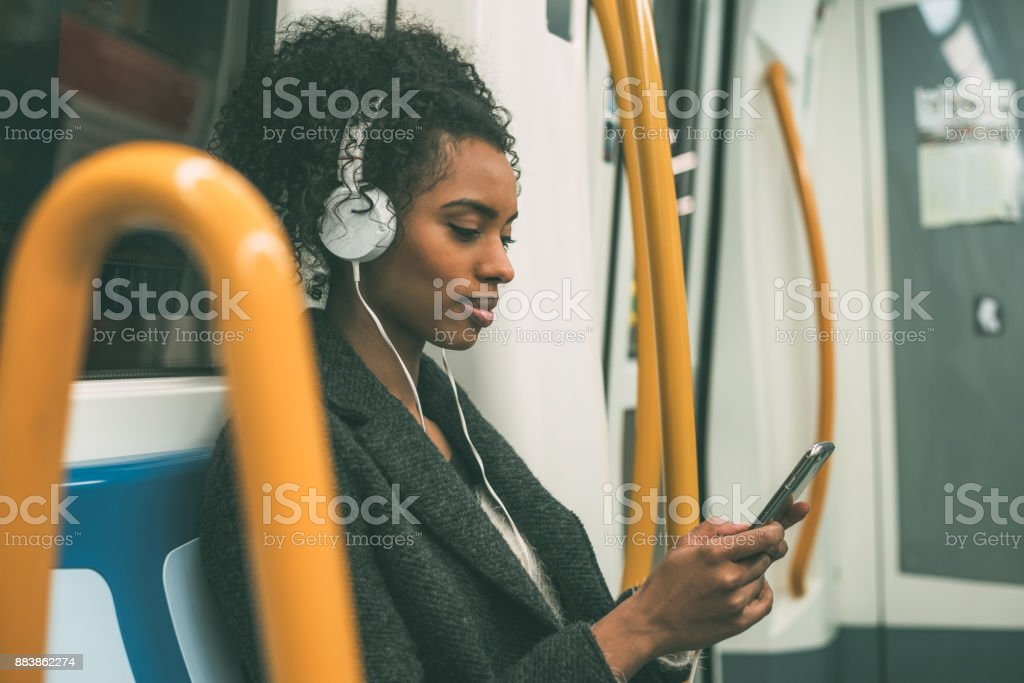 Happy young black woman sitting inside the underground listening to music 'n stock photo