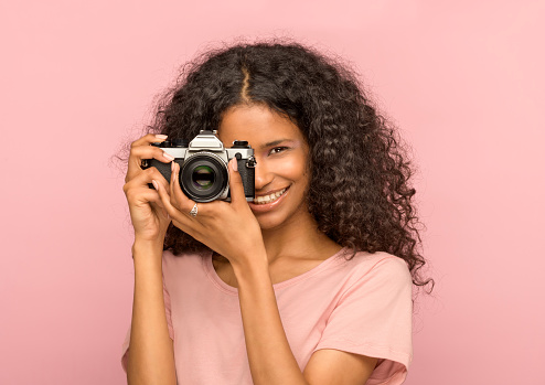 Happy attractive young black woman with a vintage camera focusing on the viewer with a beaming friendly smile against a pink studio background