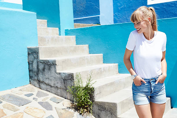 Happy young blond woman in shorts and t-shirt Happy young blond woman in shorts and t-shirt shorts stock pictures, royalty-free photos & images