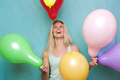 istock Happy young blond woman playing with balloons 491873843