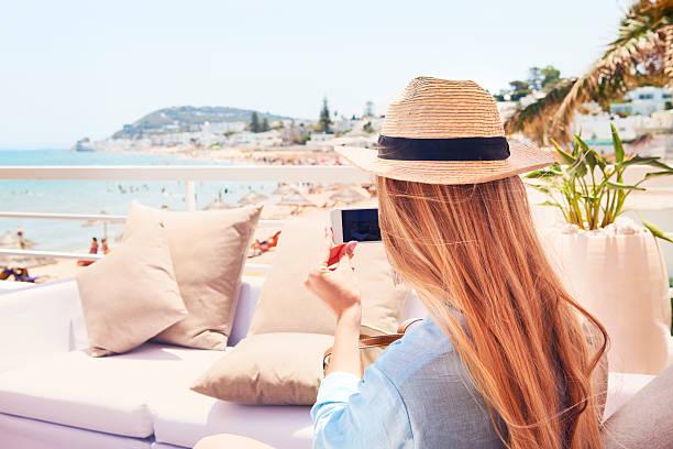 happy young blond woman taking smartphone photo with smart phone - urlaub in tunesien stock-fotos und bilder