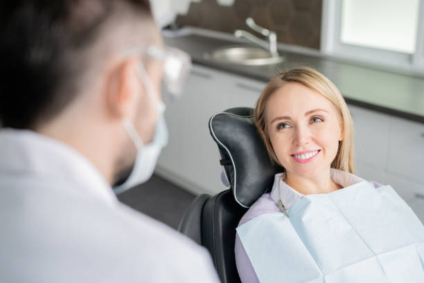 Happy young blonde female patient looking at her dentist with healthy smile Happy young blonde female patient looking at her dentist with healthy smile while sitting in armchair before examination dental health stock pictures, royalty-free photos & images